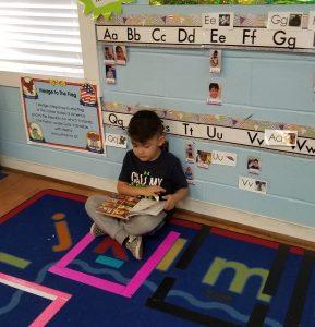 Head Start child reading a book,