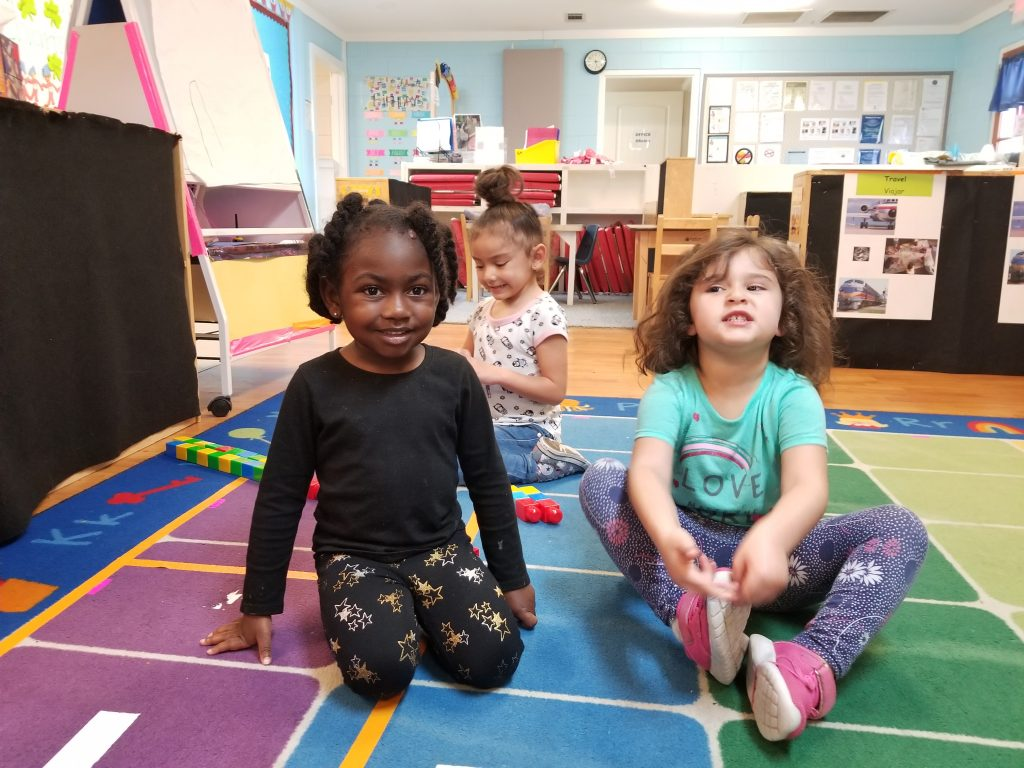 Hutto Head Start girls pose for a picture in their playroom.