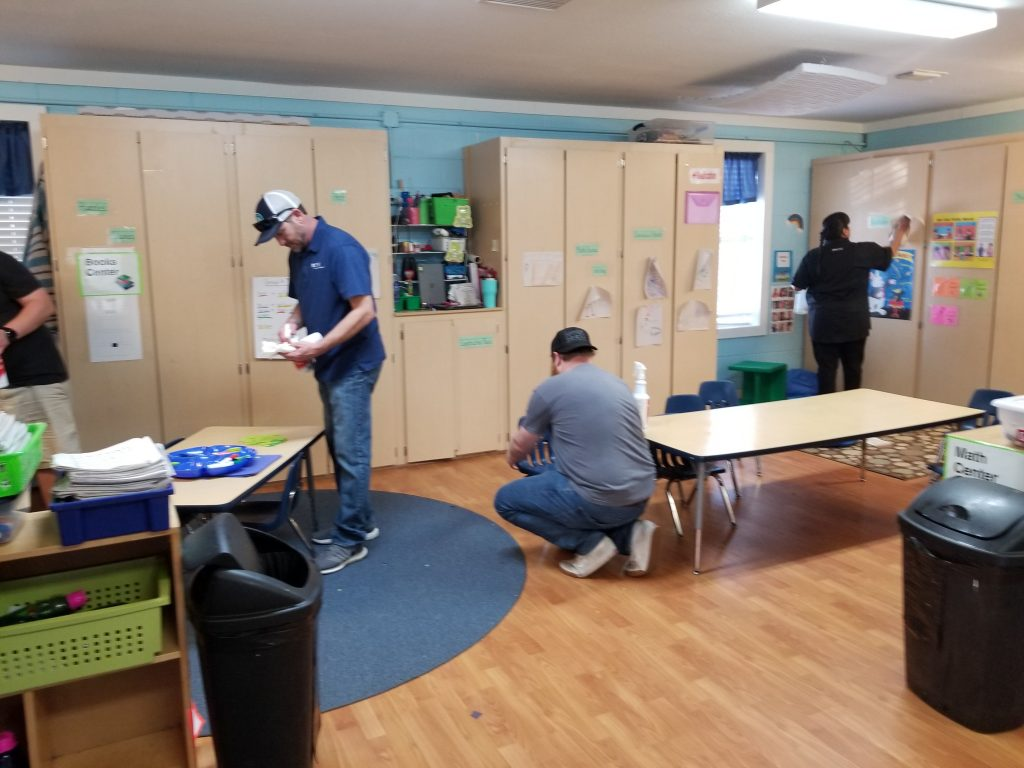 Dell volunteers cleaning inside playroom